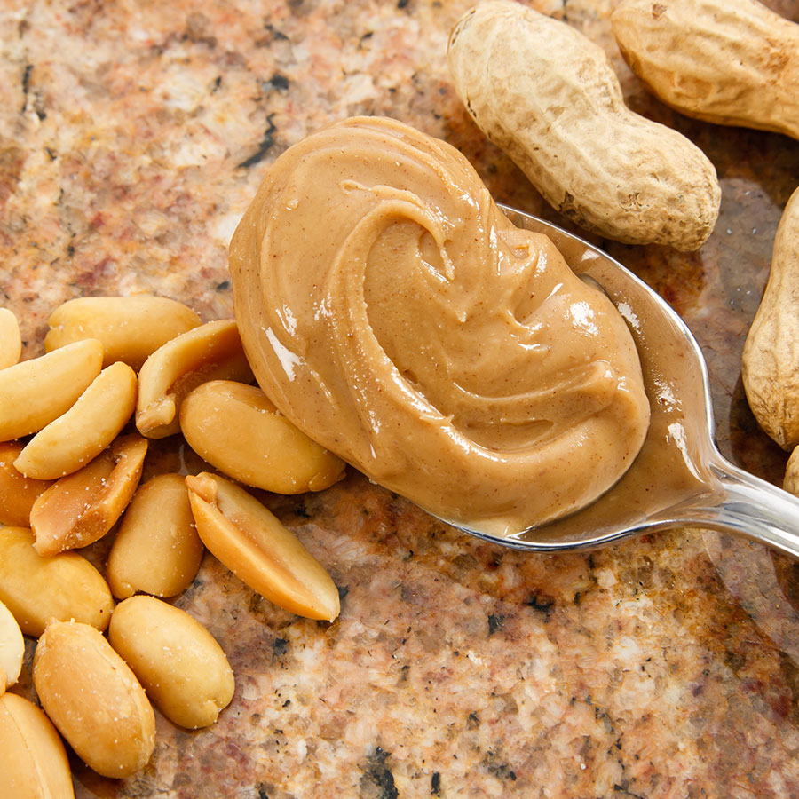Peanut Butter on a Spoon with Peanuts in the Background Sourced by Bernard for Restaurants in Canada