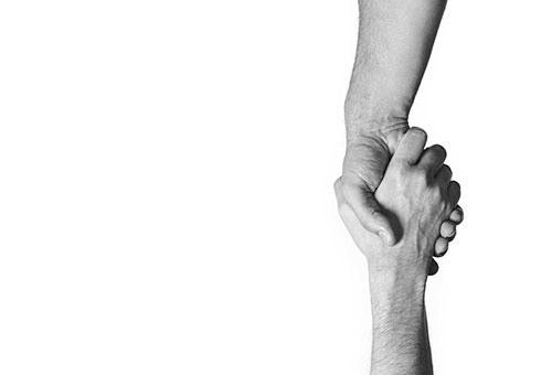 Photo of one hand helping another up symbolizing the greater goods consulting services