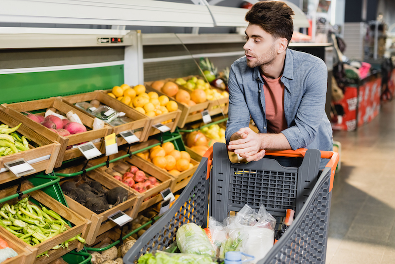 a man strolling through a fruit and vegetable section in a grocery store